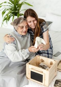 Großmutter überprüft altes spielzeug mit enkelin