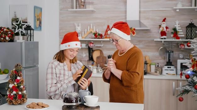 Großmutter überraschendes enkelkind mit weihnachtsverpackungsgeschenk, das die weihnachtszeit feiert