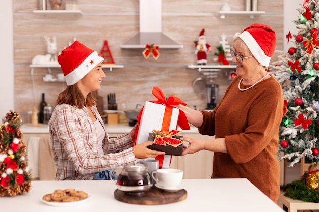 Großmutter überrascht enkelin mit weihnachtsverpackungsgeschenk