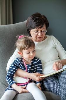 Großmutter und enkelin, die zusammen ein buch lesen und auf einem sitzsack sitzen. oma erzählt dem kleinen mädchen geschichten.