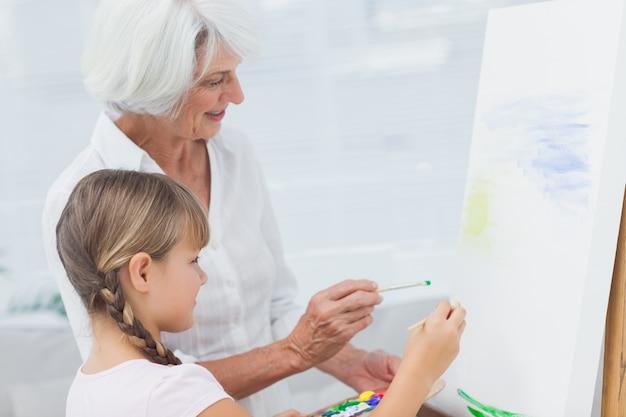 Großmutter und enkelin, die zusammen malen