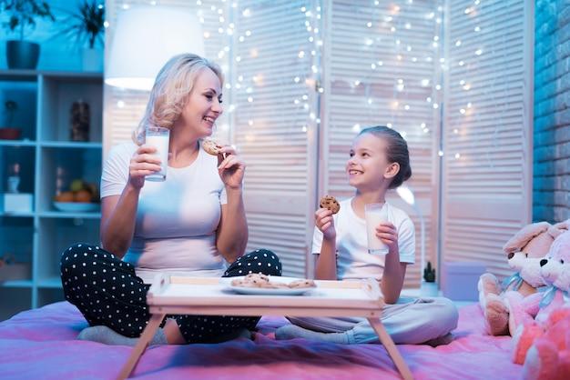 Großmutter und enkelin essen nachts zu hause kekse mit milch.