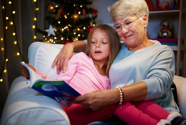 Großmutter und enkelin im sessel mit buch