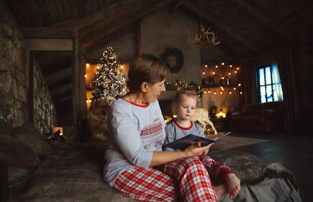 Großmutter und enkelin in den traditionellen weihnachtspyjamas, die auf dem bett im haus sitzen