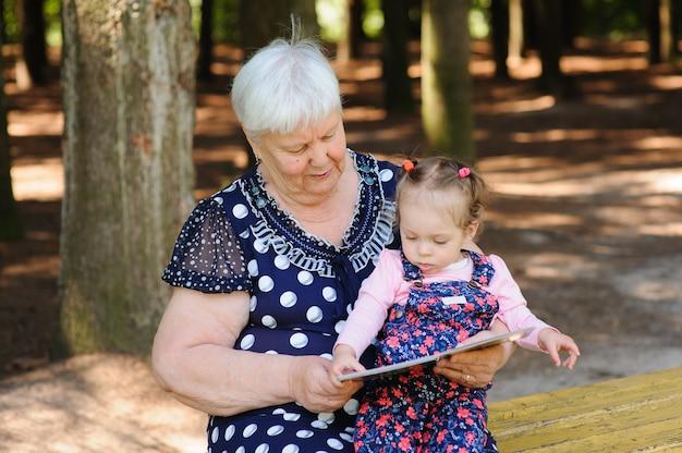 Großmutter und enkelin lesen das buch im park