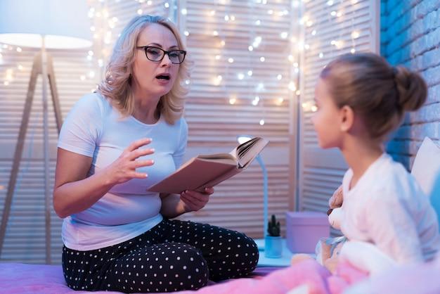 Großmutter und enkelin lesen nachts zu hause ein kinderbuch.