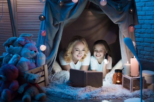 Großmutter und enkelin lesen nachts zu hause in einem deckenhaus ein buch.