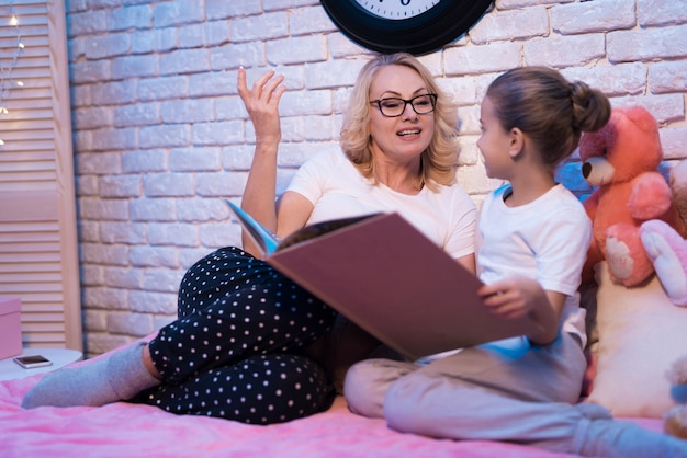 Großmutter und enkelin lesen zu hause.