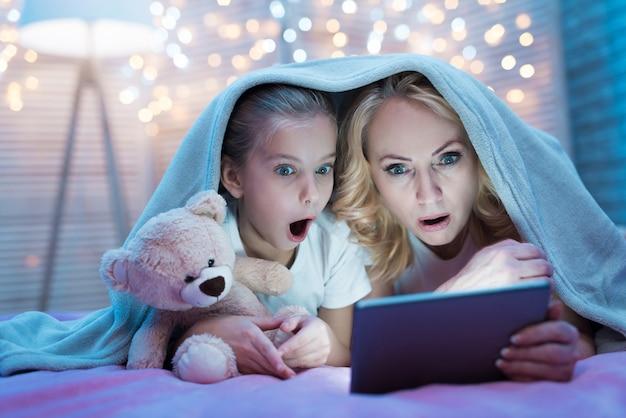 Großmutter und enkelin schauen sich einen film an.