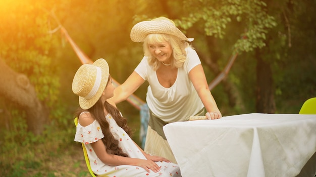 Großmutter und enkelin sind am tisch im garten