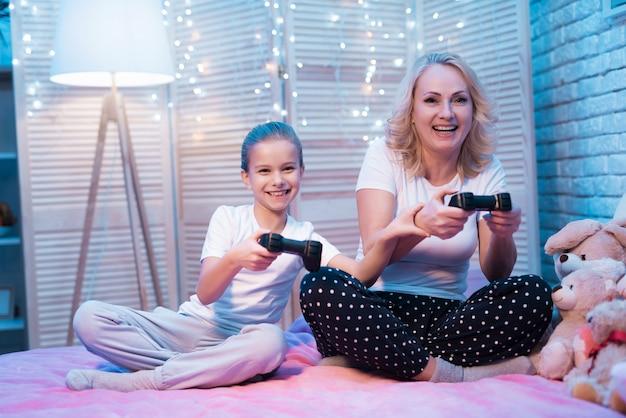 Großmutter und enkelin spielen nachts zu hause videospiele.