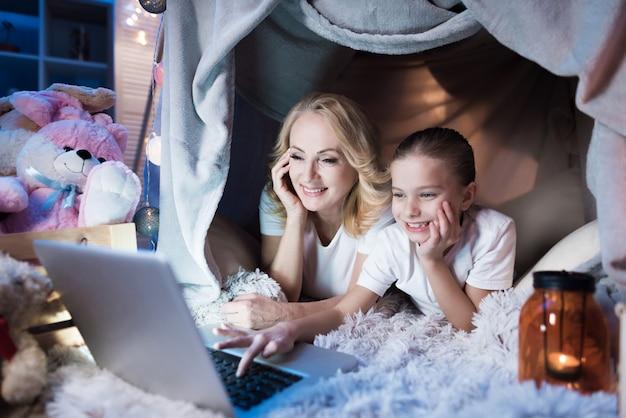 Großmutter und enkelin sprechen nachts zu hause mit der familie auf einem laptop im deckenhaus.