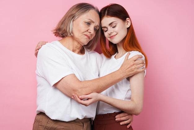 Großmutter und enkelin stehen nebeneinander familienfreundschaftsspaß rosa hintergrund