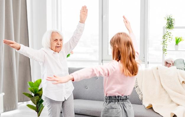 Großmutter und enkelin trainieren zusammen zu hause an einem sonnigen tag und halten die hände hoch