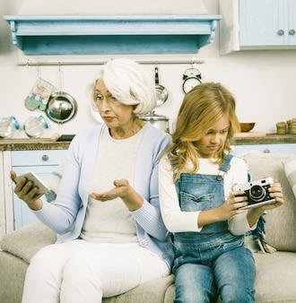 Großmutter und enkelin versuchen, kamera zu benutzen