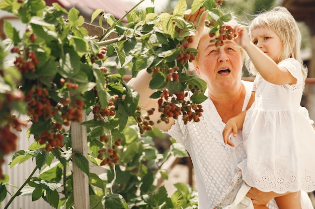Großmutter und enkelin zusammen, umarmen sich und lachen im sommer freudig in einem blühenden garten. familie im freien lebensstil.