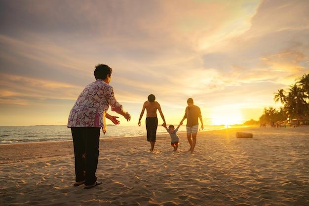 Großmutter und ihre familie spielen am strand zusammen
