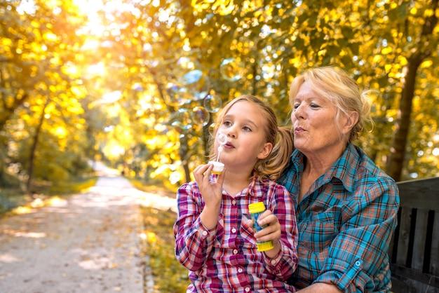Großmutter und ihre süße enkelin bläst an einem sonnigen tag seifenblasen in einem park
