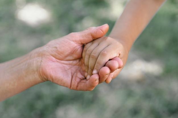 Großmutter und kind halten sich an den händen