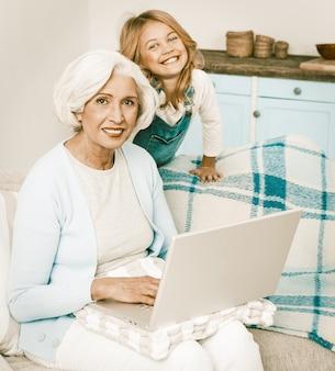 Großmutter und kleines enkelkind mit laptop zu hause