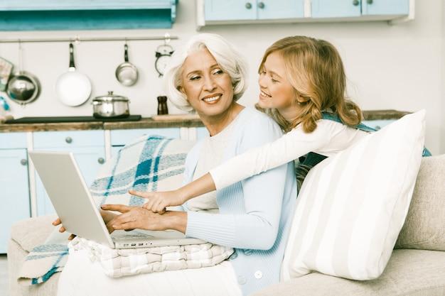Großmutter und kleines mädchen, die online mit laptop einkaufen