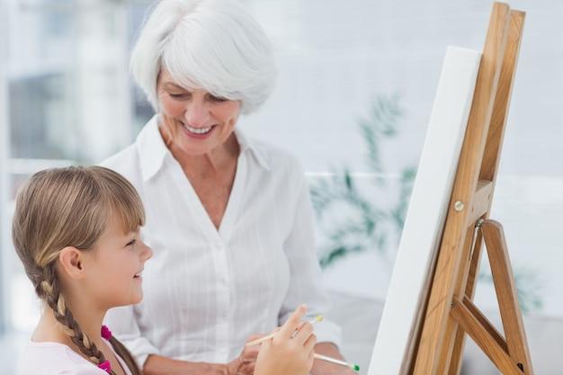 Großmutter und nette enkelin, die zusammen malen