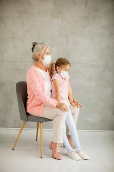 Großmutter und süße kleine enkelin tragen atemmasken