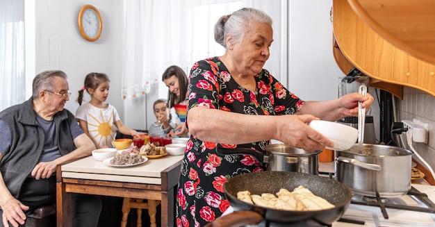 Großmutter verwöhnt ihre enkel mit einem köstlichen hausgemachten mittagessen.