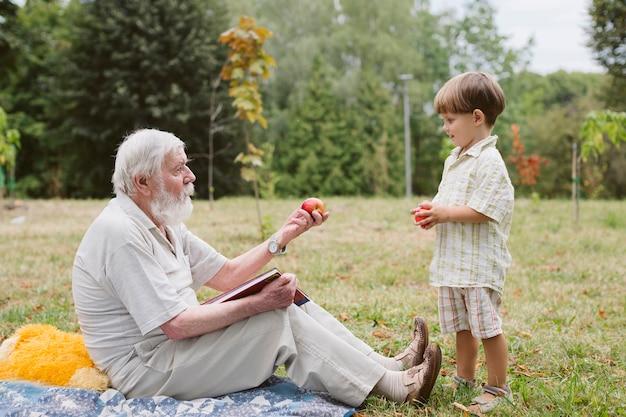 Großvater, der dem enkel apfel gibt