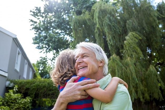 Großvater, der enkel am yard umarmt