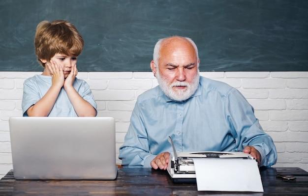 Großvater, der mit seinem enkel spricht, genießt es, mit seinem enkel mit seinem glücklichen großvater zu sprechen, um einen laptop-lehrer zu benutzen, der seinem jugendlichen schüler im bildungsunterricht hilft