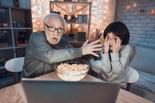 Großvater-enkel, der gruseligen film auf laptop aufpasst