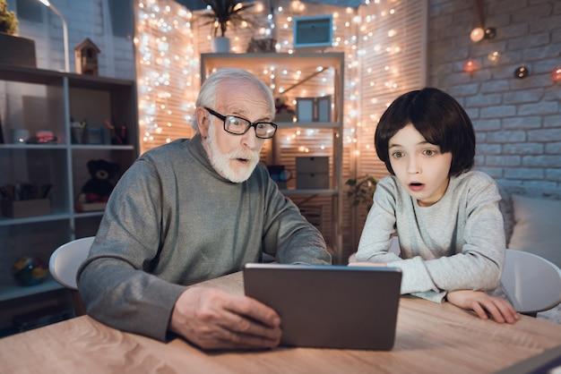 Großvater-enkel, der gruseligen film auf tablet aufpasst
