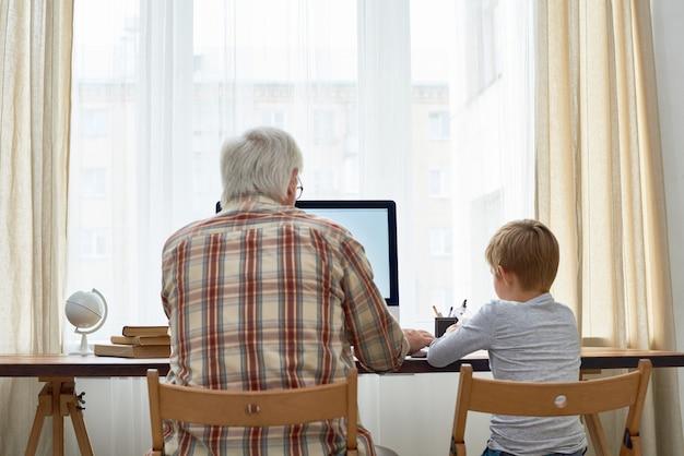 Großvater hilft kind bei den hausaufgaben