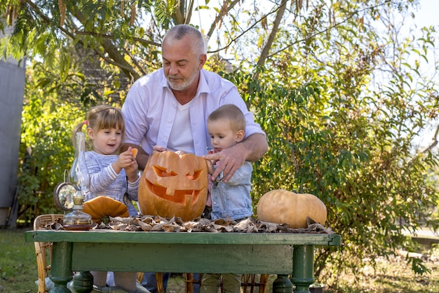 Großvater hilft kindern, einen kürbis für halloween zu schnitzen
