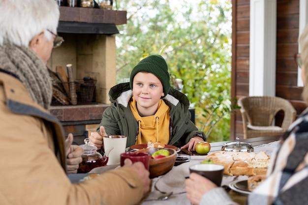 Großvater in warmer freizeitkleidung und wollstrickschal im gespräch mit enkel am bedienten tisch beim abendessen im freien im landhaus