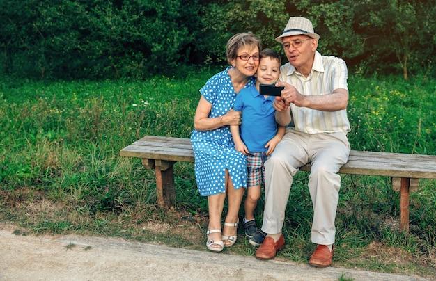 Großvater macht selfie mit großmutter und enkel sitzen auf einer bank