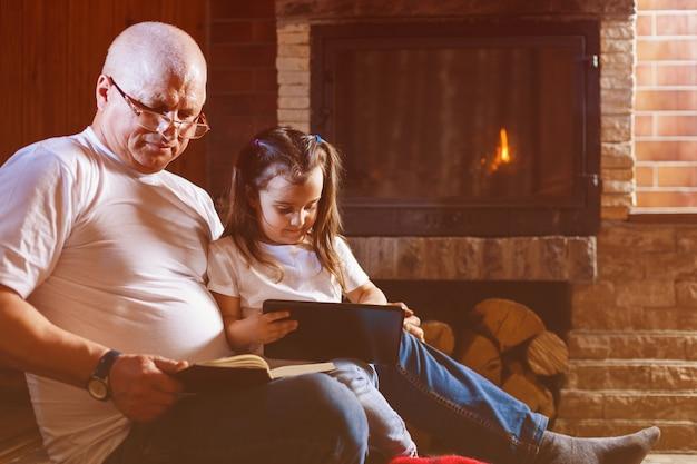 Großvater mit buch und enkelkind mit dem smartphone, der zu hause nahe dem kamin sitzt