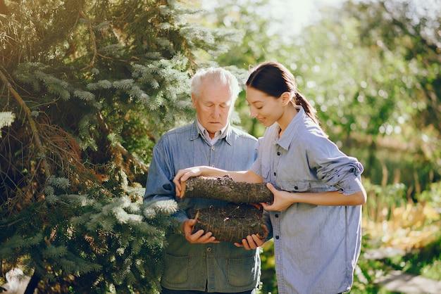 Großvater mit enkelin auf einem hof mit brennholz in händen