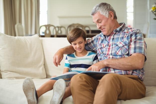 Großvater mit ihrem enkel lesebuch auf dem sofa