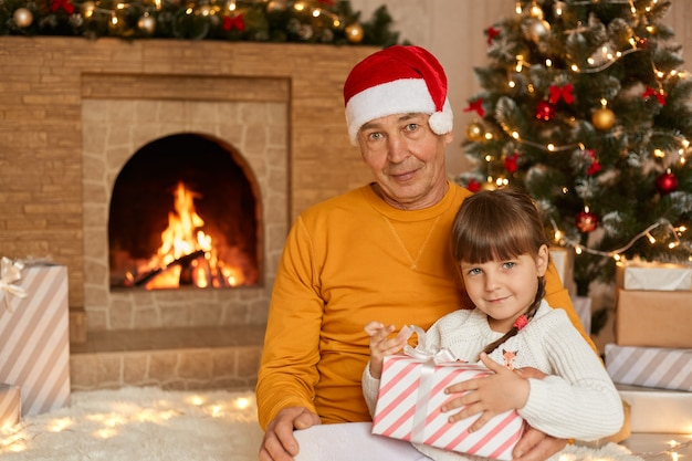 Großvater mit ihrer enkelin, die im wohnzimmer sitzt, und kind, das geschenkbox hält, auf boden auf weichem teppich nahe tanne baum und kamin posierend.