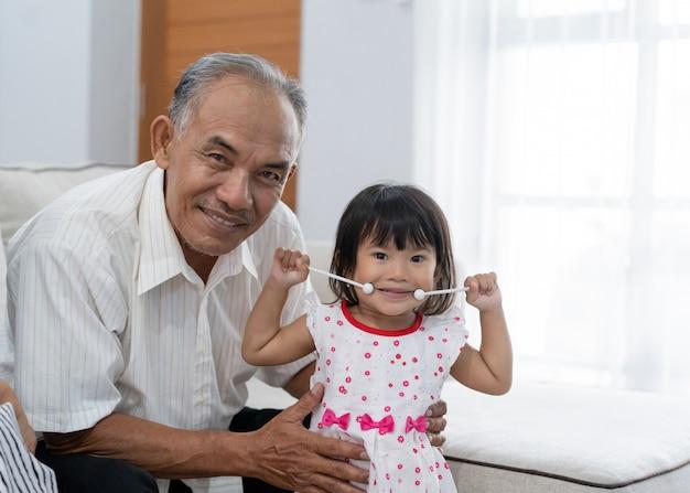 Großvater mit ihrer kleinen prinzessin, die musikinstrument hält