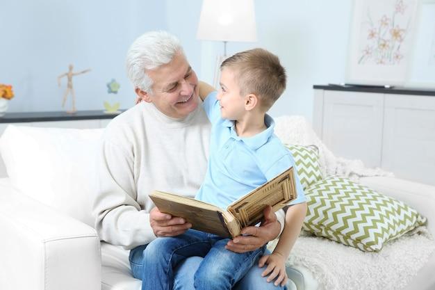 Großvater schaut sich mit seinem enkel ein fotoalbum an