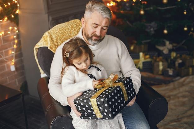 Großvater sitzt mit seiner enkelin. weihnachten feiern in einem gemütlichen haus. mann in einem weißen strickpullover.