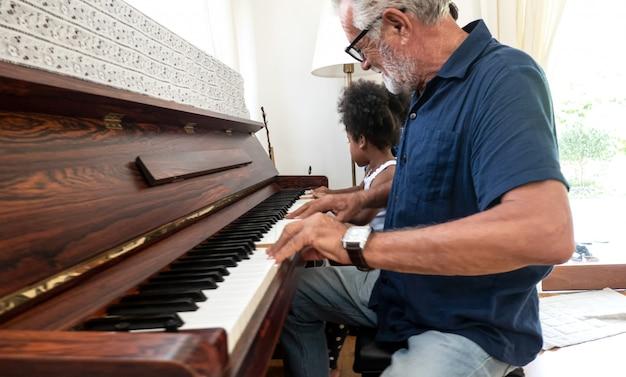 Großvater spielt klavier mit kleinem mädchen