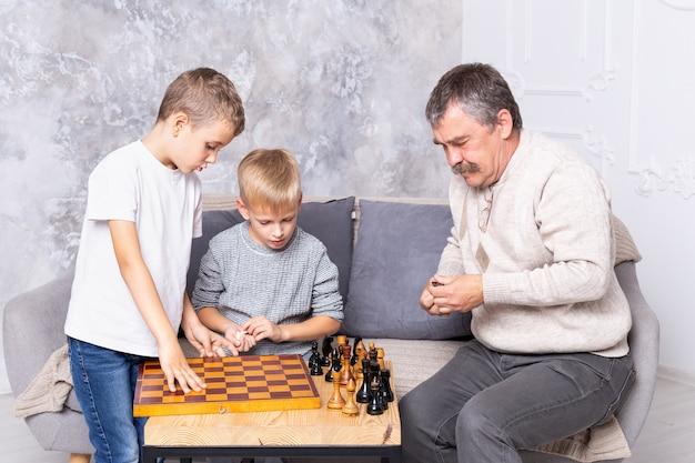 Großvater spielt schach mit enkelkindern. die jungs und der opa sitzen auf dem sofa im wohnzimmer und spielen. ein älterer mann bringt einem kind das schachspielen bei