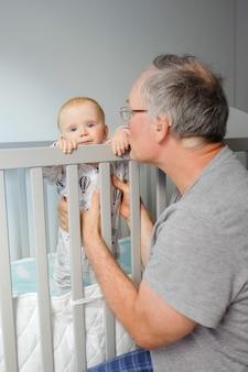 Großvater trainiert süßes baby zu stehen. kleinkind, das in der krippe steht und kamera betrachtet. vertikaler schuss. kinderbetreuung oder kindheitskonzept