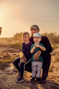 Großvater umarmt seine enkel während der maisernte. ein bauer, der seine kleinen helfer umarmt, während er auf dem feld mit mais kniet. hilfe auf dem maisfeld.