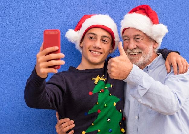 Großvater umarmt seinen enkel im teenageralter, während beide eine weihnachtsmütze tragen und lächeln, während sie ein selfie machen
