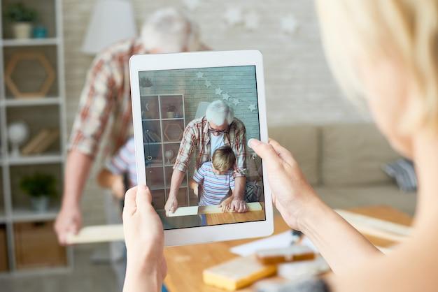 Großvater und enkel auf dem bildschirm des digitalen tablets